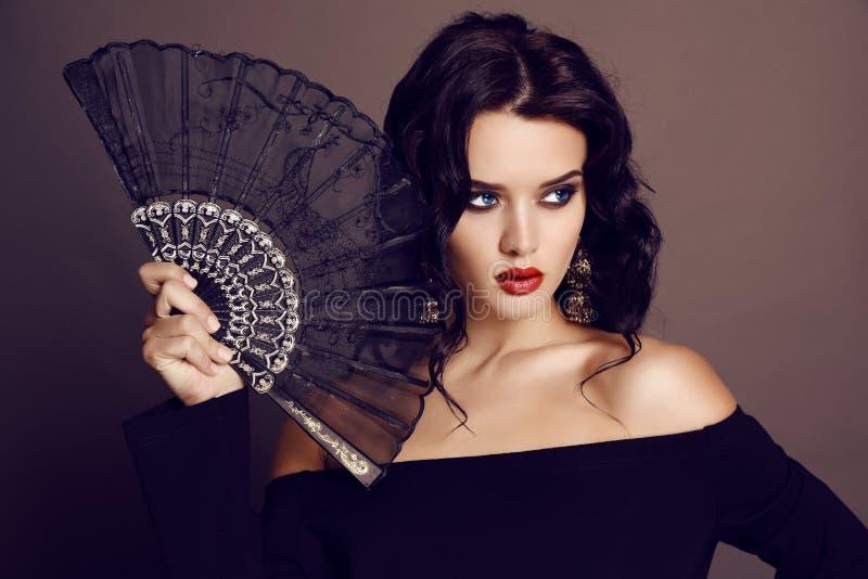 La belle femme sensuelle avec les cheveux foncés tenant la dentelle noire éventent à disposition photographie stock