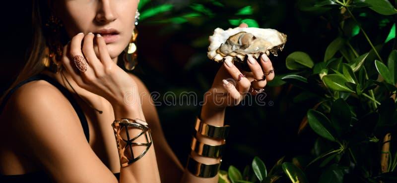 La belle femme sexy de brune de mode dans le restaurant intérieur cher mangent des huîtres photographie stock libre de droits