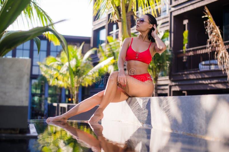 La belle femme sexy mince utilisant le bikini rouge détendent près de la piscine d'eau extérieure sur la station de vacances photos libres de droits