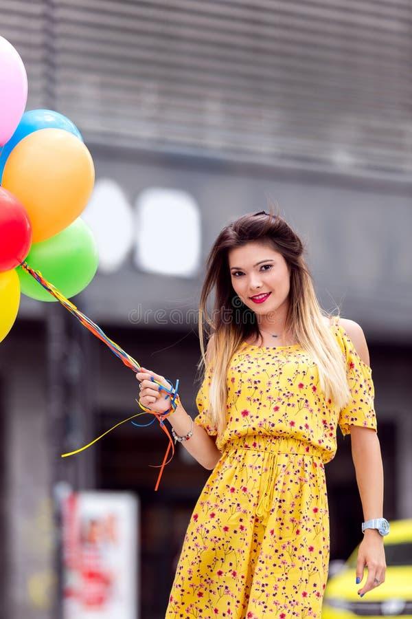 La belle femme smilling avec beaucoup de ballons à disposition images stock