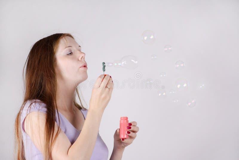 La belle femme souffle des bulles de savon image stock
