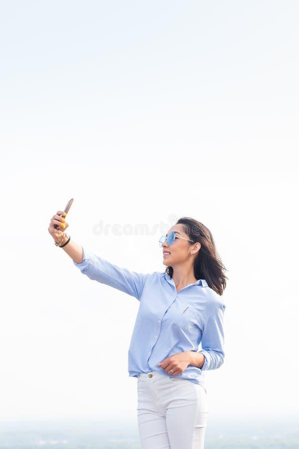 La belle femme tenant un smartphone et prend un selfie, regarde avec un sourire l'appareil-photo contre le ciel blanc sur la rue, photographie stock