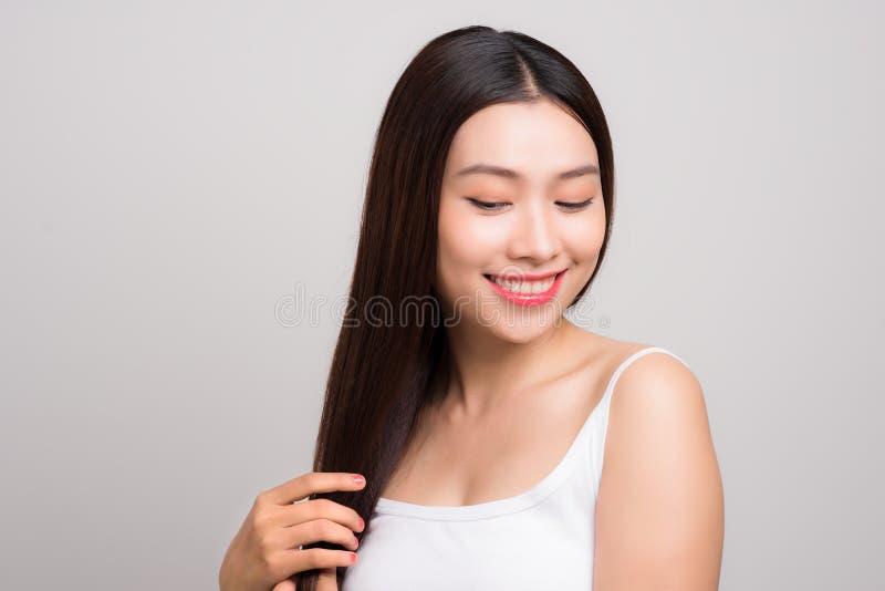 La belle femme touchent ses longs soins capillaires droits de santé avec le SM photo stock