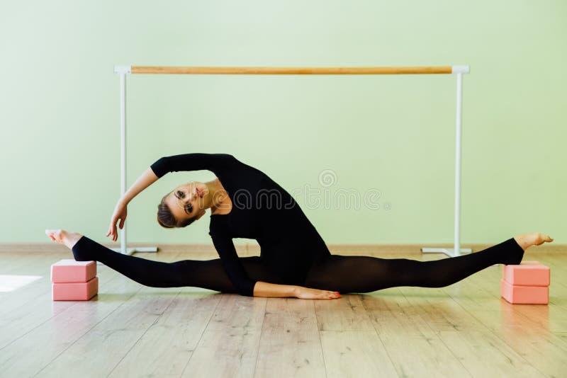La belle fille élégante de danseur classique avec le corps parfait s'assied sur le plancher image libre de droits