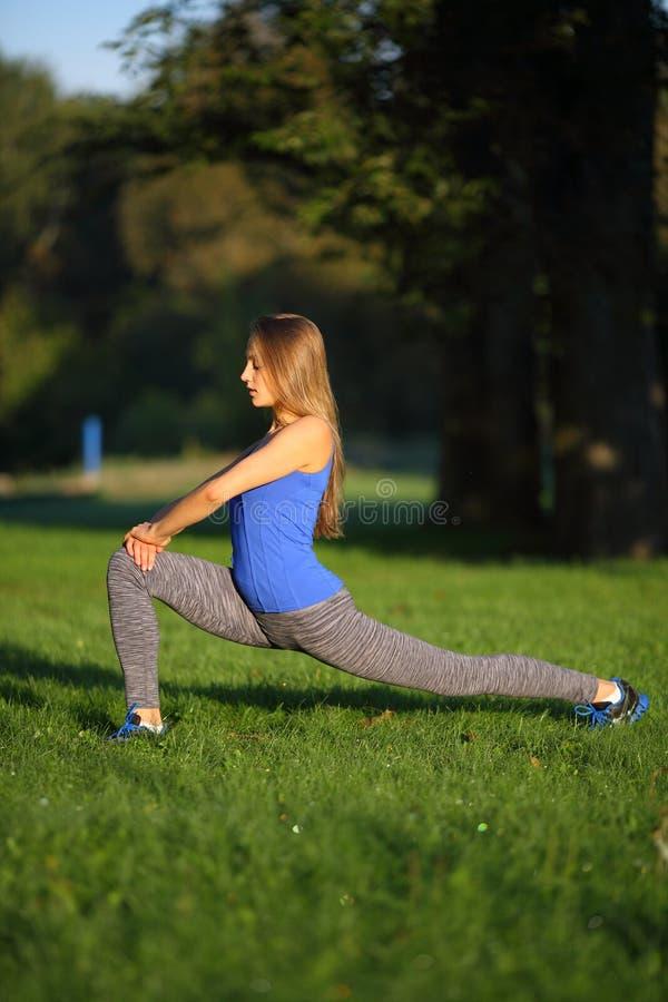 La belle fille étire les jambes en parc photo libre de droits