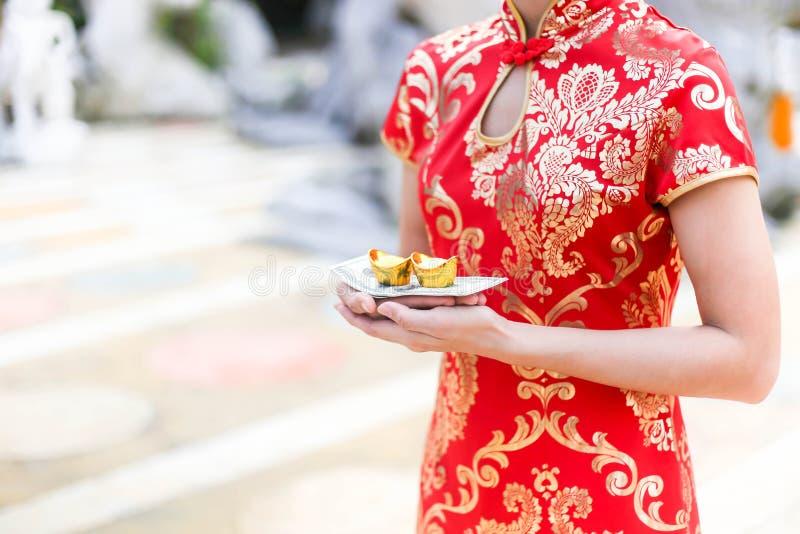 La belle fille asiatique portant la robe rouge de Cheongsam tenant le sac et l'argent d'or représente le plus fort photographie stock libre de droits