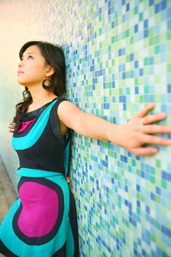 La belle fille asiatique se penchent en arrière sur le mur bleu photos stock