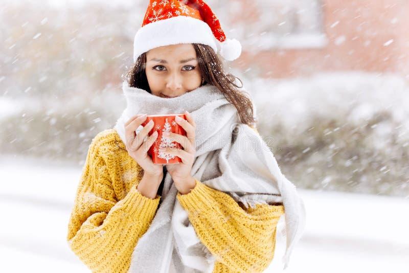 La belle fille aux cheveux foncés dans un chandail jaune, une écharpe blanche dans le chapeau de Santa Claus se tient avec une ta images stock