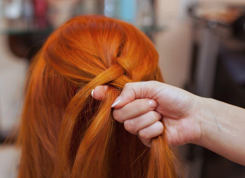 La belle fille avec de longs cheveux rouges, coiffeuse tisse une tresse française, dans un salon de beauté image libre de droits