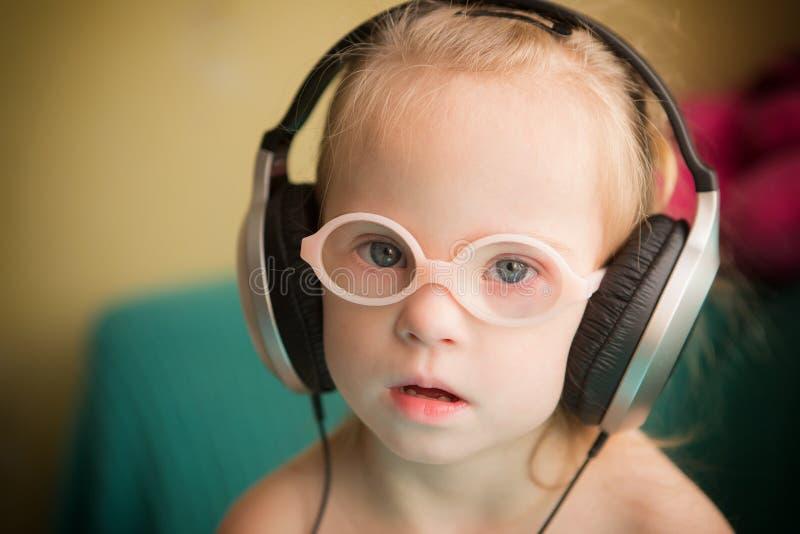 La belle fille avec la trisomie 21 écoute la musique sur des écouteurs images stock