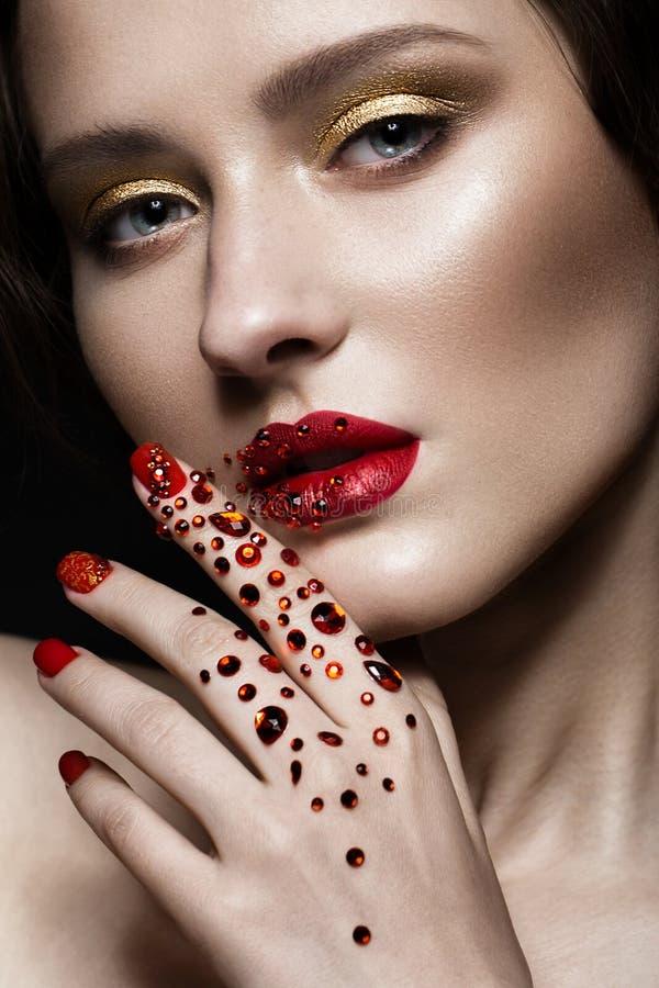 La belle fille avec le maquillage de soirée, les lèvres rouges dans les fausses pierres et la conception manicure des ongles Visa photos libres de droits
