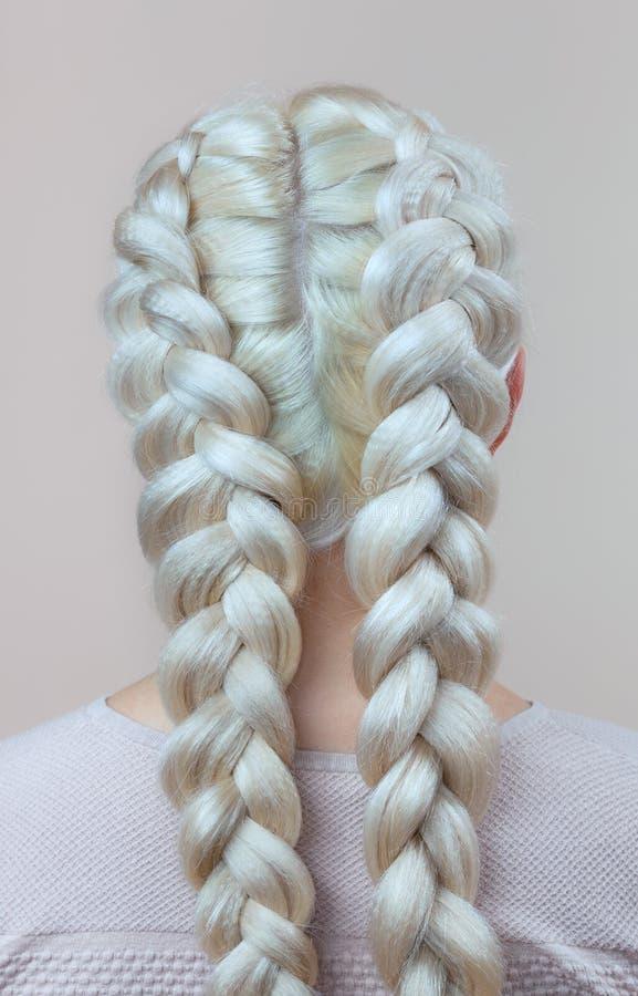 La belle fille avec les cheveux blonds, coiffeuse tisse un plan rapproché de tresse, dans un salon de beauté images stock