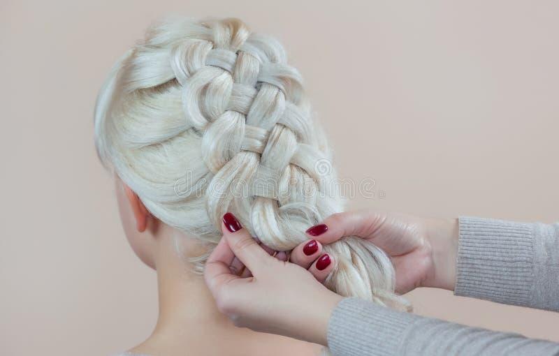La belle fille avec les cheveux blonds, coiffeuse tisse un plan rapproché de tresse, dans un salon de beauté image libre de droits