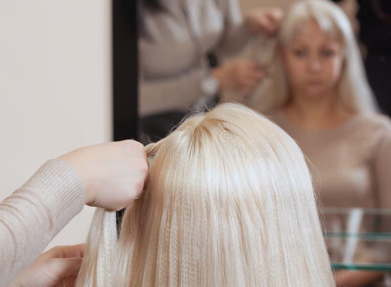 La belle fille avec les cheveux blonds, coiffeuse tisse un plan rapproché de tresse, dans un salon de beauté image stock