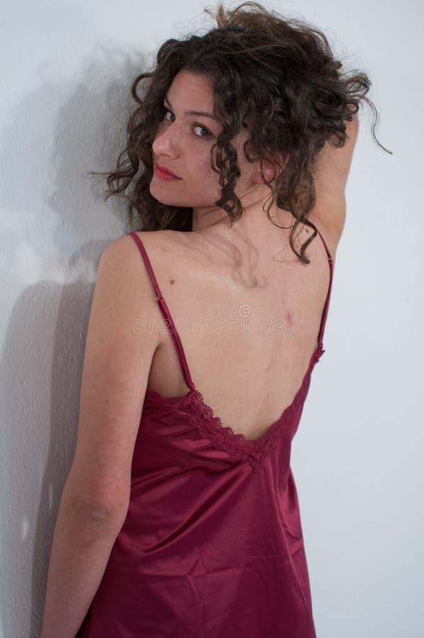 La belle fille avec les cheveux bruns déplacés, le petticoa rouge de satin, s'est retournée du dos contre le mur blanc uniforme image stock