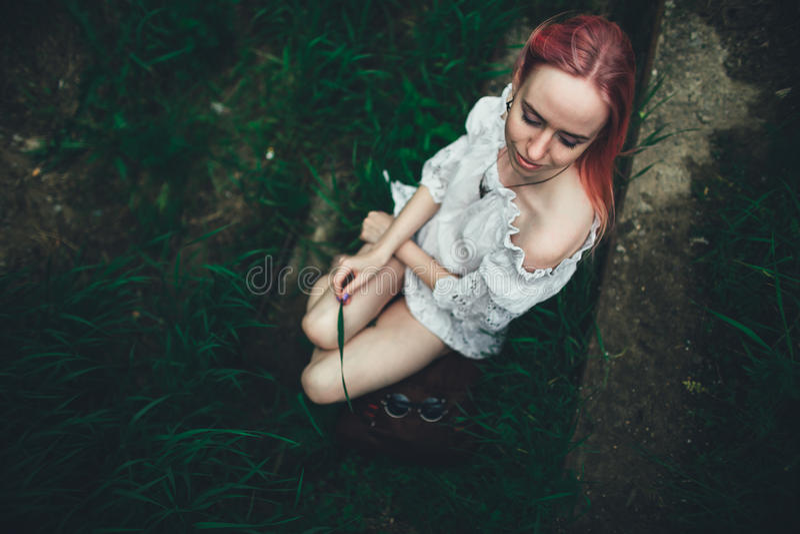 La belle fille avec les cheveux roses s'assied sur l'échelle jetée dans un environnement d'une herbe verte image stock