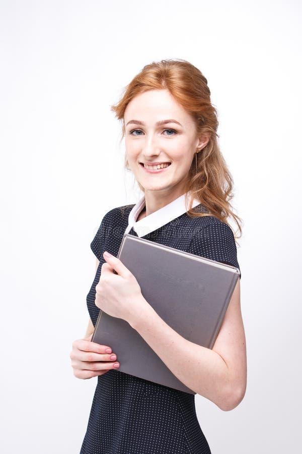 La belle fille avec les cheveux rouges et le livre gris dans des mains habillées dans le blanc de robe noir a isolé le fond photo stock