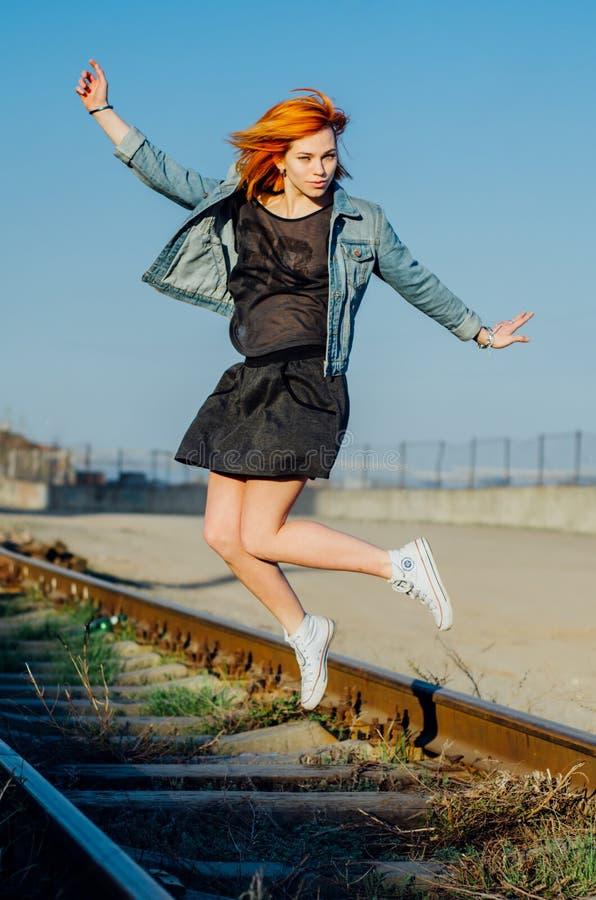 La belle fille avec les cheveux rouges saute dans un jour ensoleillé, le modèle photos stock