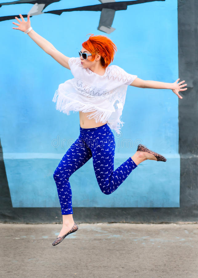 La belle fille avec les cheveux rouges saute dans un jour ensoleillé, modèle image stock