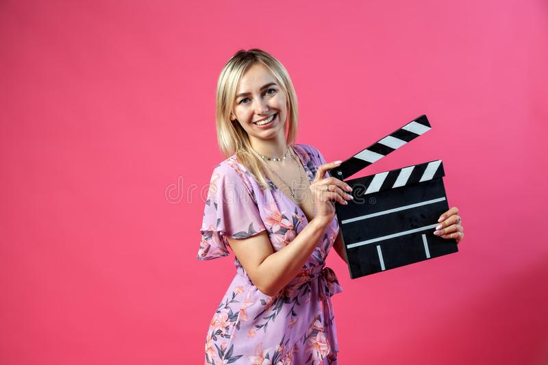 La belle fille blonde dans un bain de soleil pourpre tient un cinéaste ouvert de claquette dans le noir avec les rayures blanches images stock
