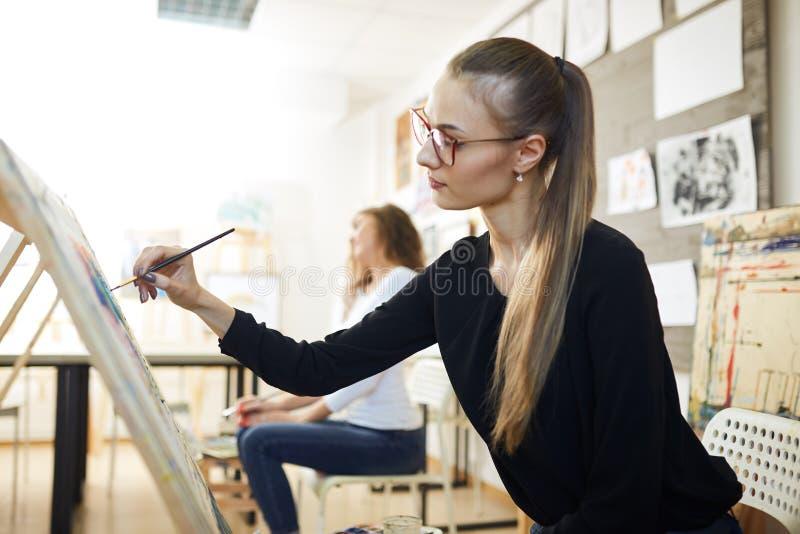 La belle fille blonde en verres habill?s dans le chemisier noir s'assied au chevalet et peint un tableau dans le studio d'art photos stock