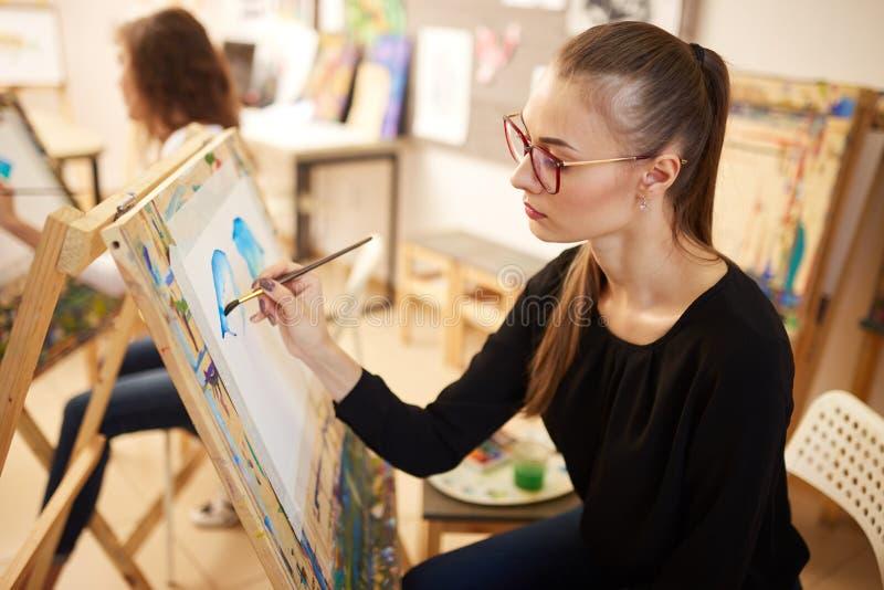 La belle fille blonde en verres habill?s dans le chemisier noir s'assied au chevalet et peint un tableau dans le studio d'art images stock