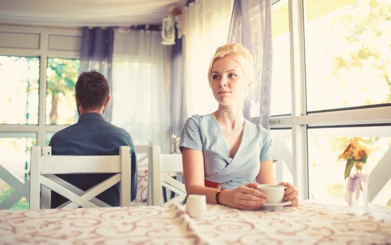 La belle fille blonde s'assied en café à la table, tient la tasse images stock