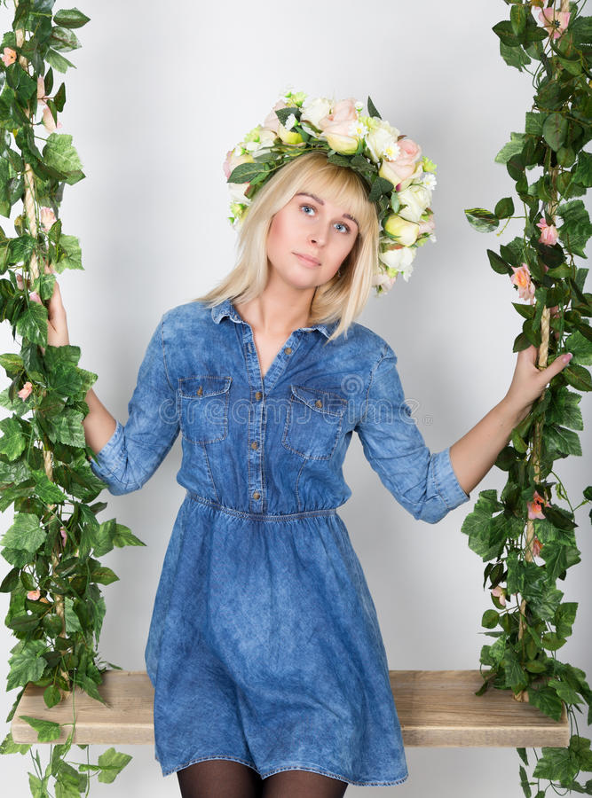 La belle fille blonde s'est habillée dans le bain de soleil de denim, sa tête une guirlande des fleurs image stock