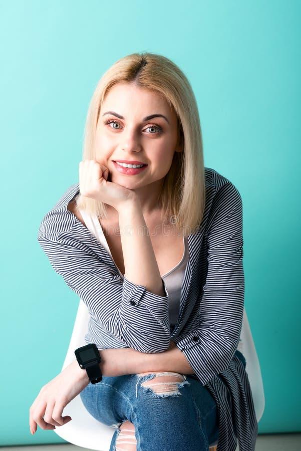 La belle fille blonde se repose sur la chaise image libre de droits