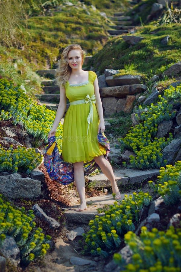 La belle fille blonde se trouvant parmi le ressort fleurit photos stock