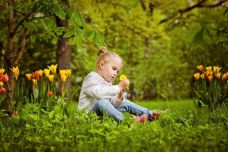 La belle fille blonde très douce s'assied près du lit de fleur du rouge images stock