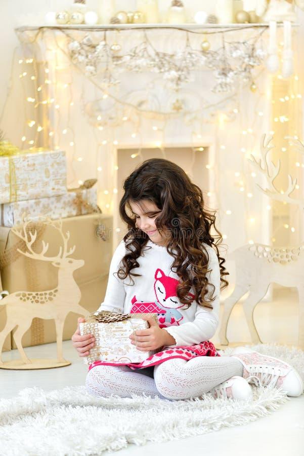 La belle fille bouclée avec le plaisir admire les lumières magiques de guirlandes de Noël d'or et les décorations d'arbre ouvrant photo stock