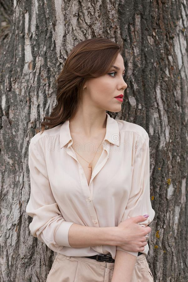 La belle fille caucasienne avec les lèvres rouges dans le chemisier beige élégant regarde pensivement de côté Concept de solitude photo libre de droits