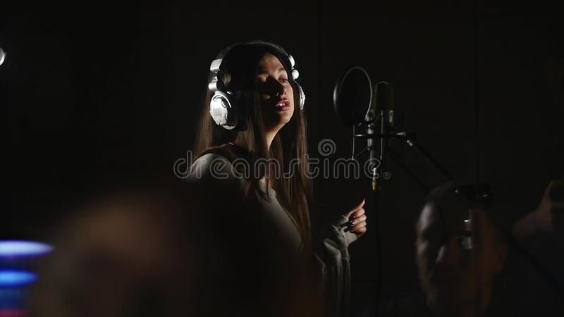 La belle fille chante dans le studio avec l'ingénieur support image libre de droits