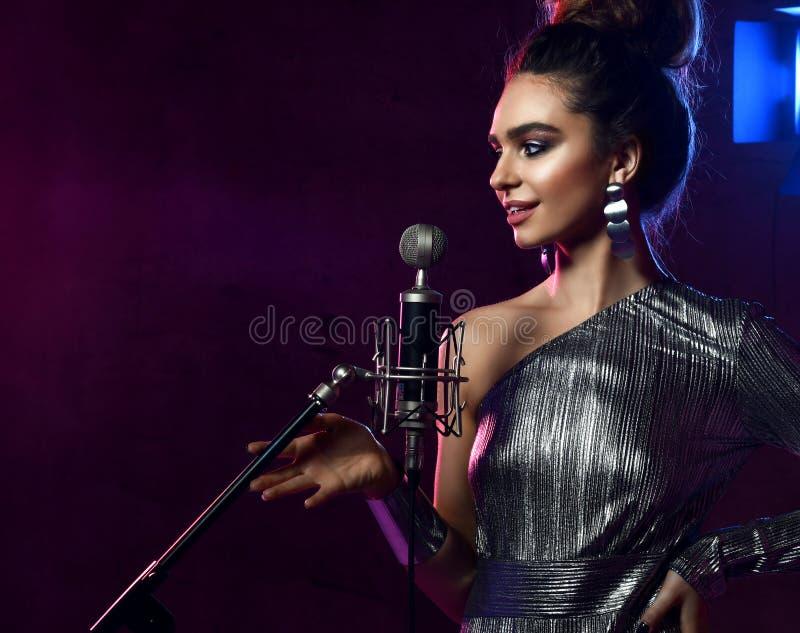 La belle fille chanteuse chanteur Afro boucl? de cheveux chantent avec la chanson de karaoke de microphone sur l'?tape sur la lam image stock