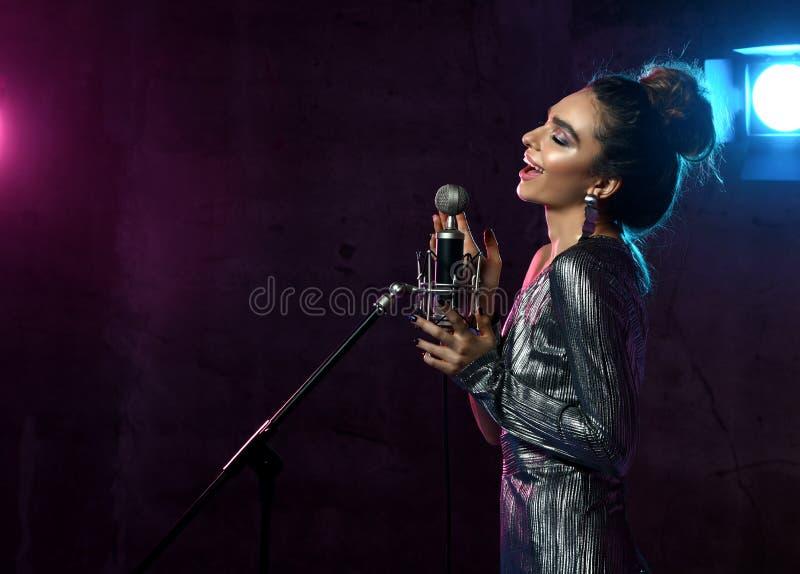 La belle fille chanteuse chanteur Afro boucl? de cheveux chantent avec la chanson de karaoke de microphone sur l'?tape sur la lam images libres de droits