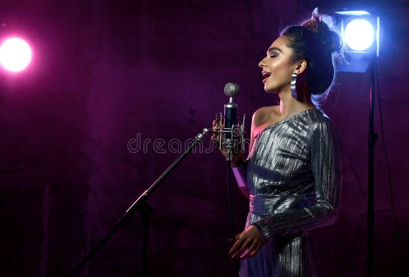 La belle fille chanteuse chanteur Afro boucl? de cheveux chantent avec la chanson de karaoke de microphone sur l'?tape sur la lam photo stock