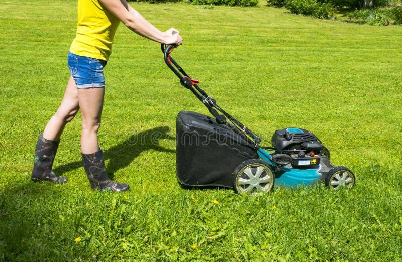 La belle fille coupe la pelouse, les pelouses de fauchage, tondeuse à gazon sur l'herbe verte, équipement d'herbe de faucheuse, f photographie stock