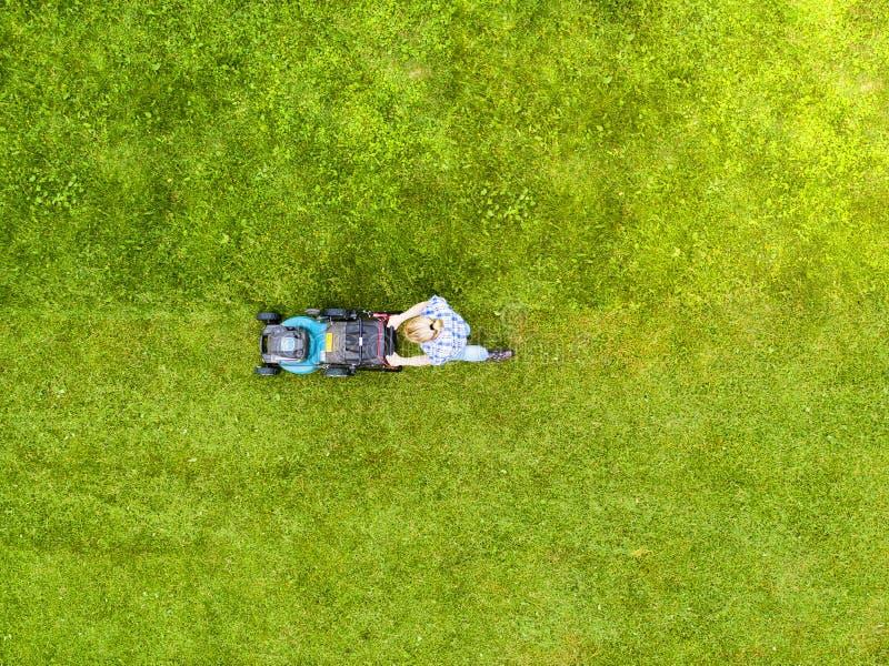 La belle fille coupe la pelouse Pelouses de fauchage Belle tondeuse à gazon de femme de vue aérienne sur l'herbe verte ?quipement photographie stock