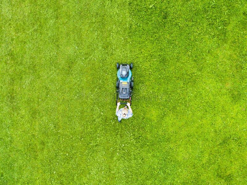La belle fille coupe la pelouse Pelouses de fauchage Belle tondeuse à gazon de femme de vue aérienne sur l'herbe verte ?quipement photo stock