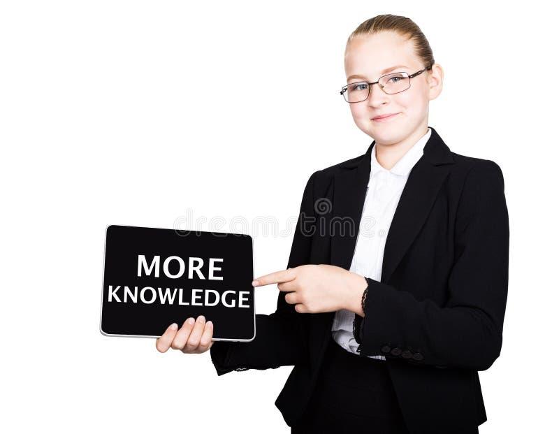 La belle fille d'école dans un costume tient un comprimé de PC dans des ses mains et le regard dans l'appareil-photo, sur un comp image libre de droits