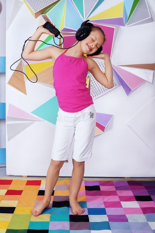 La belle fille d'enfant gai dans des écouteurs chante et danse Th photos stock