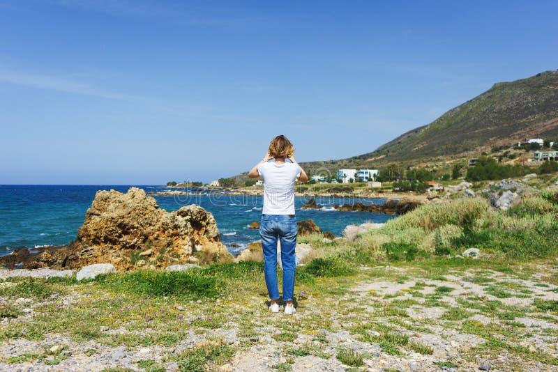 La belle fille dans des jeans en voyage par la mer prend des photos du paysage sur son smartphone pour les réseaux sociaux photographie stock