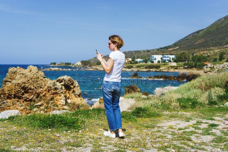 La belle fille dans des jeans en voyage par la mer prend des photos du paysage sur son smartphone pour les réseaux sociaux photo libre de droits