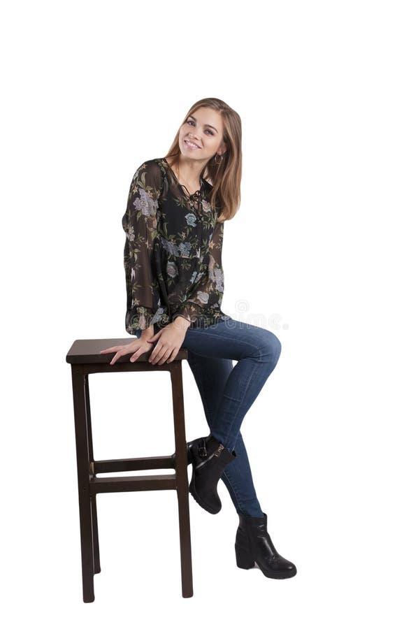 La belle fille dans des jeans s'assied sur un mode de vie de main de chaise photographie stock