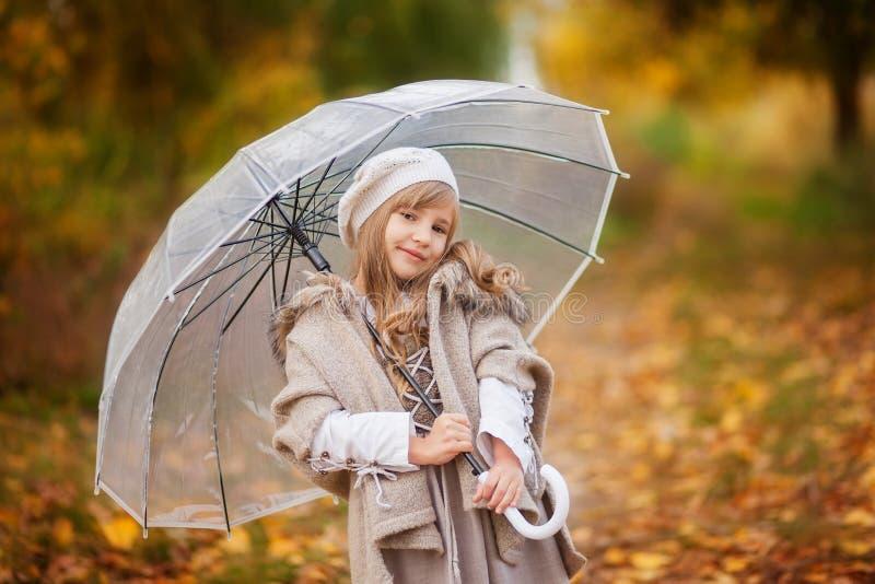 La belle fille dans l'équipement de cru avec un parapluie transparent marche en parc d'automne, fond orange photo libre de droits