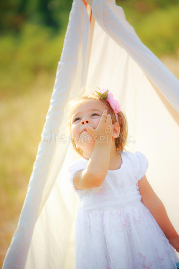 La belle fille dans la robe de fête blanche se tient en main et joue photographie stock libre de droits