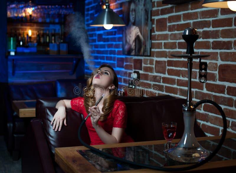 La belle fille dans la robe de soirée fume un narguilé à l'intérieur de la barre photo stock