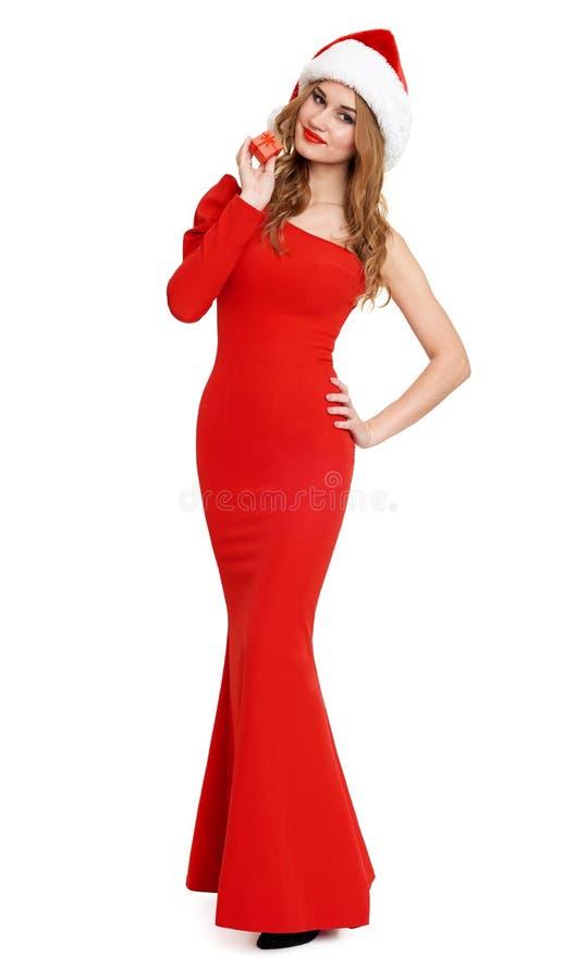La belle fille dans la robe rouge et le chapeau de Santa d'isolement sur le fond blanc, concept de vacances de Noël, montrent peu photo libre de droits