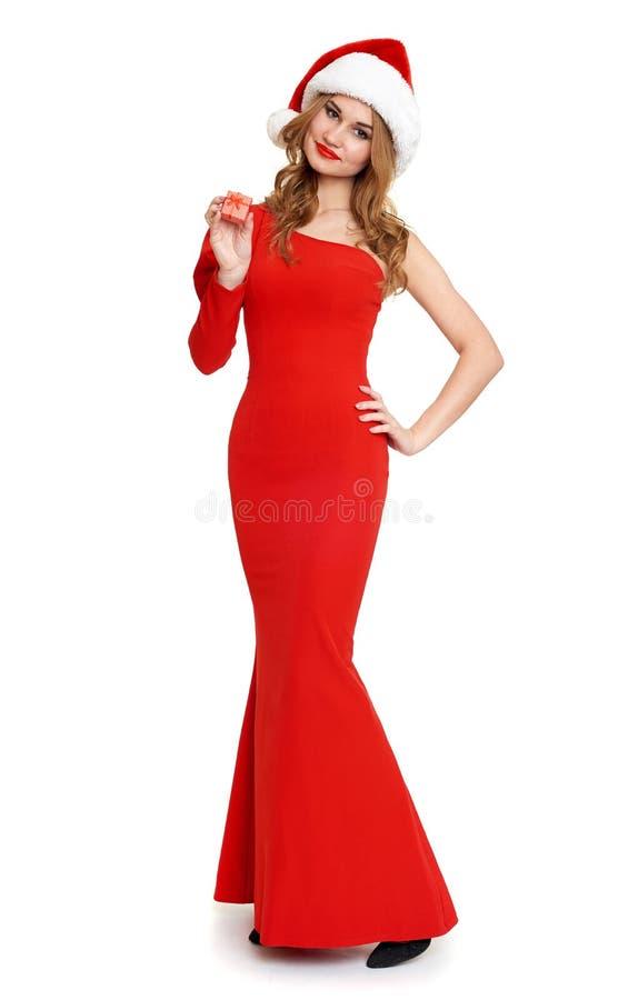 La belle fille dans la robe rouge et le chapeau de Santa d'isolement sur le fond blanc, concept de vacances de Noël, montrent peu photographie stock libre de droits